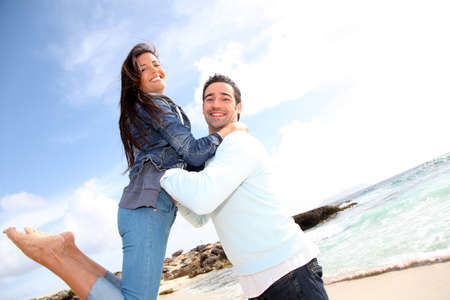 man carrying woman: Man lifting his girlfriend up in arms by the beach