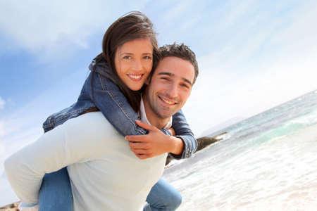 Man giving piggyback ride to girlfriend on the beach photo