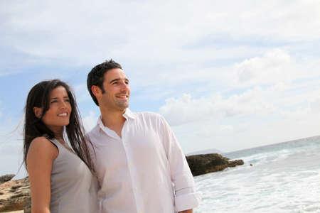 Happy couple walking by caribbean beach photo