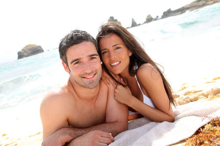 Portrait of romantic couple laying on the beach Stock Photo - 13029975