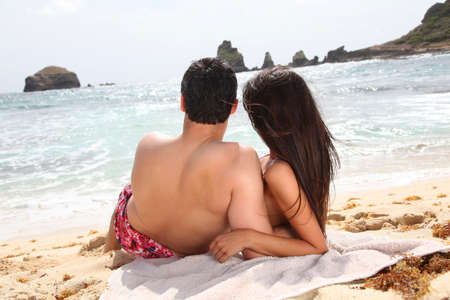 Back view of couple looking at the sea photo