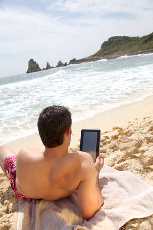 laying on back: Man using electronic tablet on the beach Stock Photo