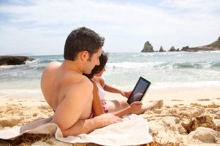 man on beach: Couple at the beach using electronic tablet Stock Photo