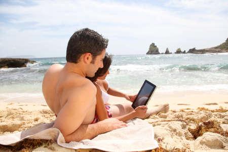fiestas electronicas: Pareja en la playa que usa la tableta electrónica Foto de archivo