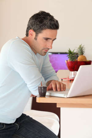 Man at home connected on internet with laptop photo
