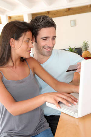 secured payment: Couple at home doing online shopping with laptop Stock Photo