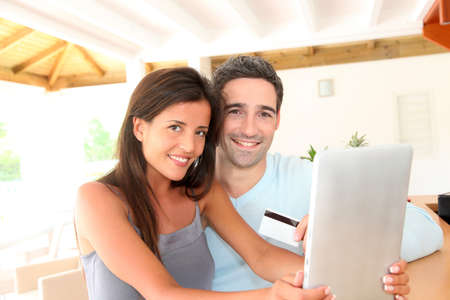 Couple at home doing online shopping with tablet Stock Photo - 13030686