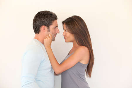 Woman pulling on boyfriend's cheeks photo