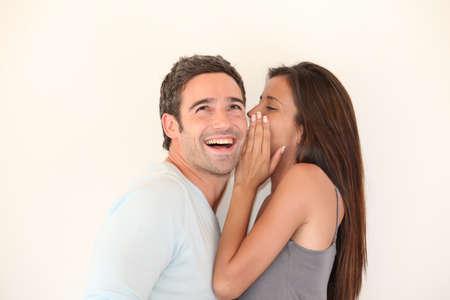 Beautiful woman whispering to boyfriends ear