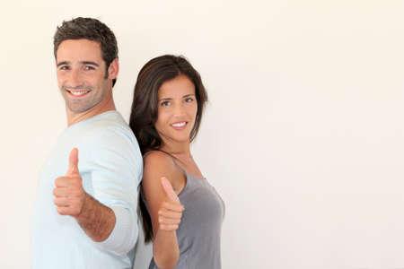 actitud positiva: Pareja de moda de pie sobre fondo blanco con el pulgar hacia arriba Foto de archivo