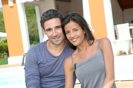 brand new: Young couple sitting in front of brand new home Stock Photo
