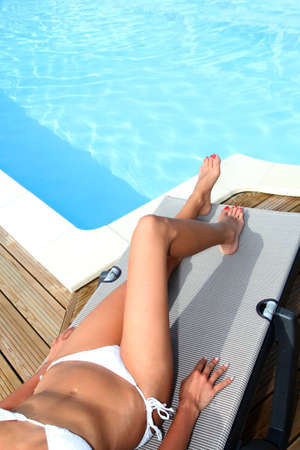 pool deck: Closeup on legs of woman relaxing in deck chair by pool