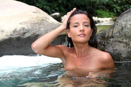 nude outdoors: Beautiful woman washing her hair in river