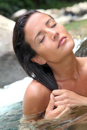 Beautiful woman washing her hair in river photo