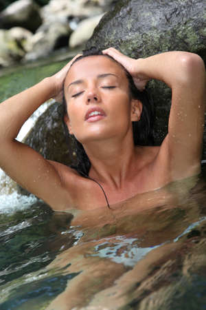 Glamorous woman showering in natural springs photo