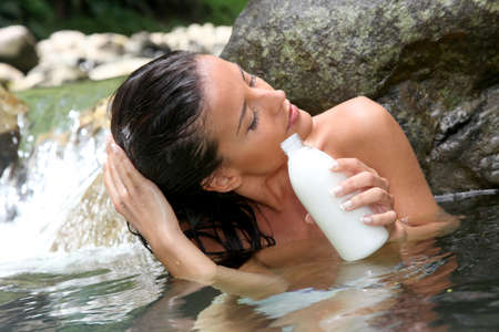 Gorgeous girl in river applying hair conditioner  photo