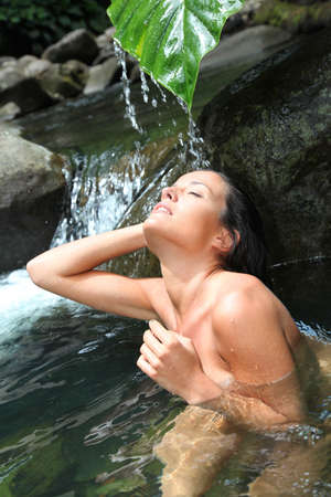 Beautiful girl showering in river under waterfall photo