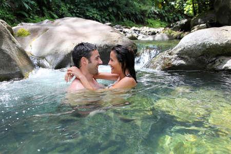 Couple having a bath in fresh river water