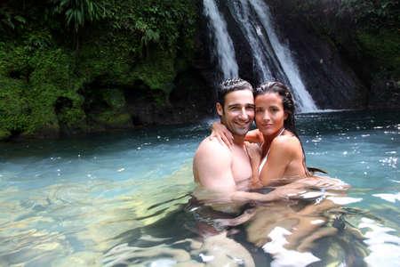 Gelukkig paar baden in de buurt van waterval op eilanden
