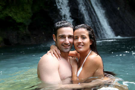 Happy couple bathing near waterfall in island photo