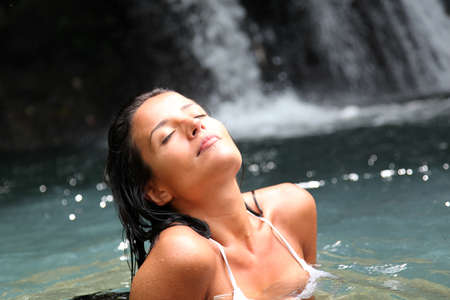 Beautiful woman enjoying bathing near natural waterfall photo