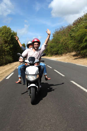 Couple enjoying scooter ride on country road photo