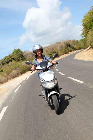 riding helmet: Young woman riding motorbike Stock Photo