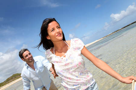 Cheerful couple walking by the sea photo
