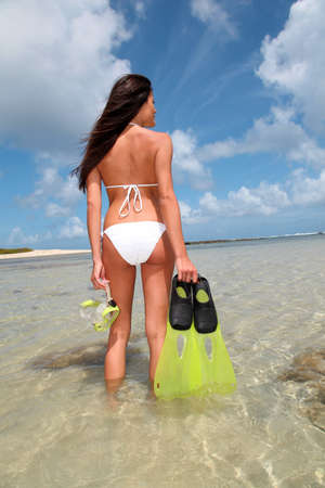 bikini island: Back view of woman holding snorkeling accessories by the sea Stock Photo
