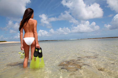 guadeloupe: Back view of woman holding snorkeling accessories by the sea Stock Photo
