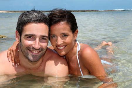 pareja de esposos: Pareja Alegre se relaja en agua de la laguna