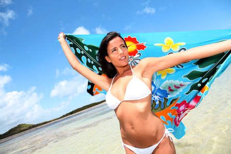 pareo: Woman at the beach holding sarong up in the air