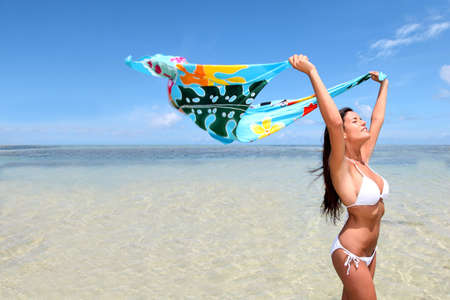Woman at the beach holding sarong up in the air photo