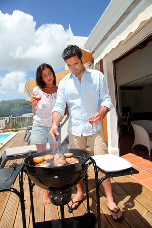 barbecue party: Young couple cooking dinner on barbecue grill