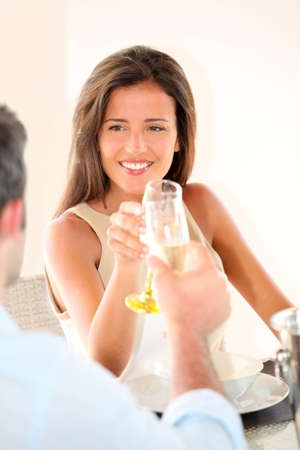 champaign: Woman cheering with glass of champaign in fancy restaurant