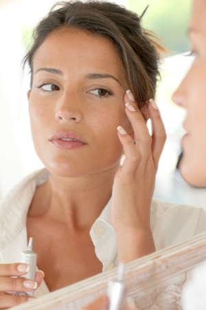 mujer maquillandose: Retrato de mujer hermosa aplicación de la crema antiarrugas