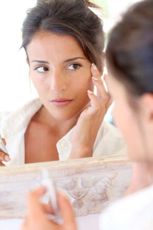 Portrait of beautiful woman applying anti-wrinkles cream photo