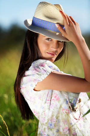 Gypsy girl with hat standing in field of wild flowers