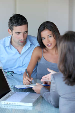 financial adviser: Couple in office signing contractual documents Stock Photo