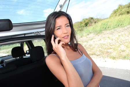 Young woman calling for car assistance on the road photo