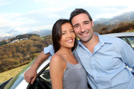 drivers: Couple standing by car on the road Stock Photo