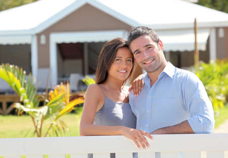 Couple standing in front of new home photo