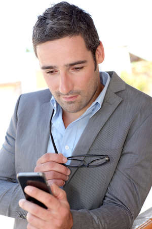 Businessman using mobilephone out in town photo