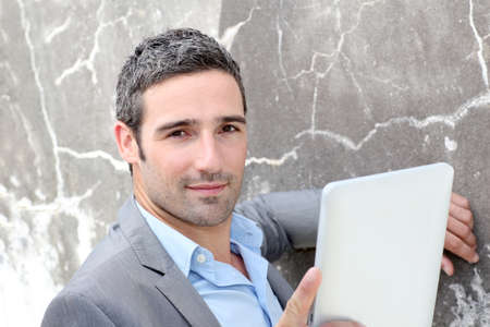 android tablet: Businessman using electronic tablet outside the office Stock Photo
