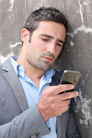 Businessman talking on mobile phone against wall photo