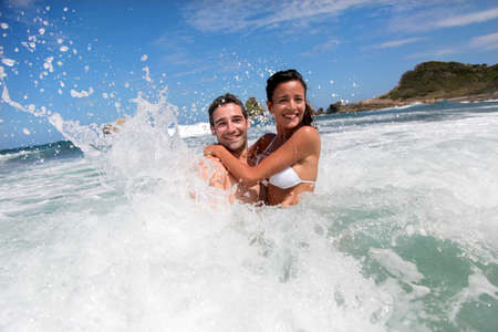 luna de miel: Pareja alegre disfrutando de las olas Foto de archivo