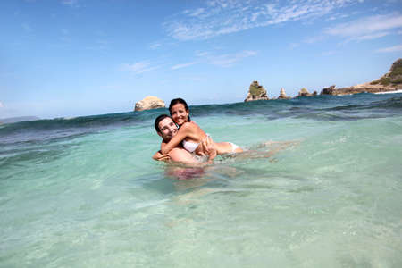 Cheerful couple swimming in the ocean photo