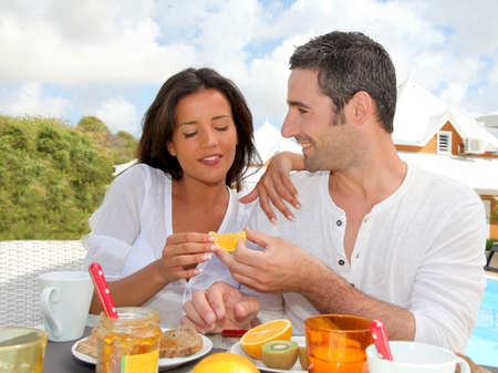 Cheerful couple taking breakfast on the outdoor terrace photo