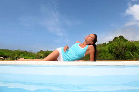 suntanning: Brunette girl in fitness outfit relaxing by the pool