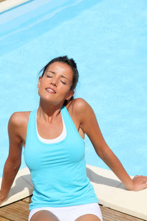 Brunette girl in fitness outfit relaxing by the pool photo